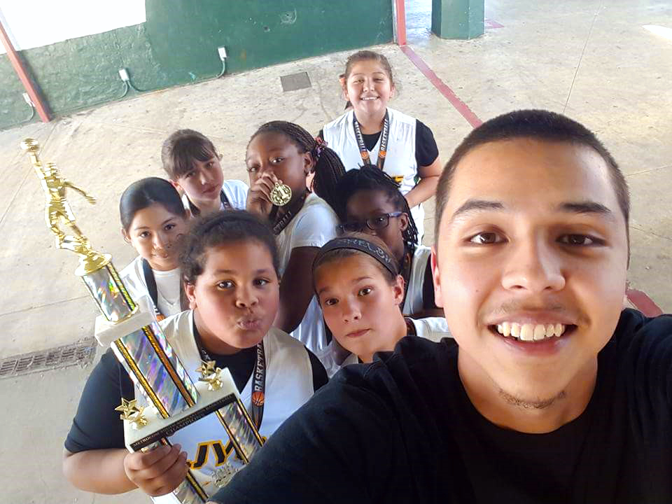 A Terry Scholar is smiling for a selfie with a group of kids, one holding a large trophy, in the background