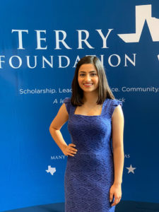 Terry Scholar in a formal blue dress, standing in front of a Terry Foundation backdrop.