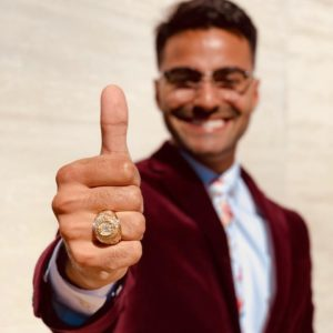 Terry Scholar smiling with thumb up and Aggie ring in focus.